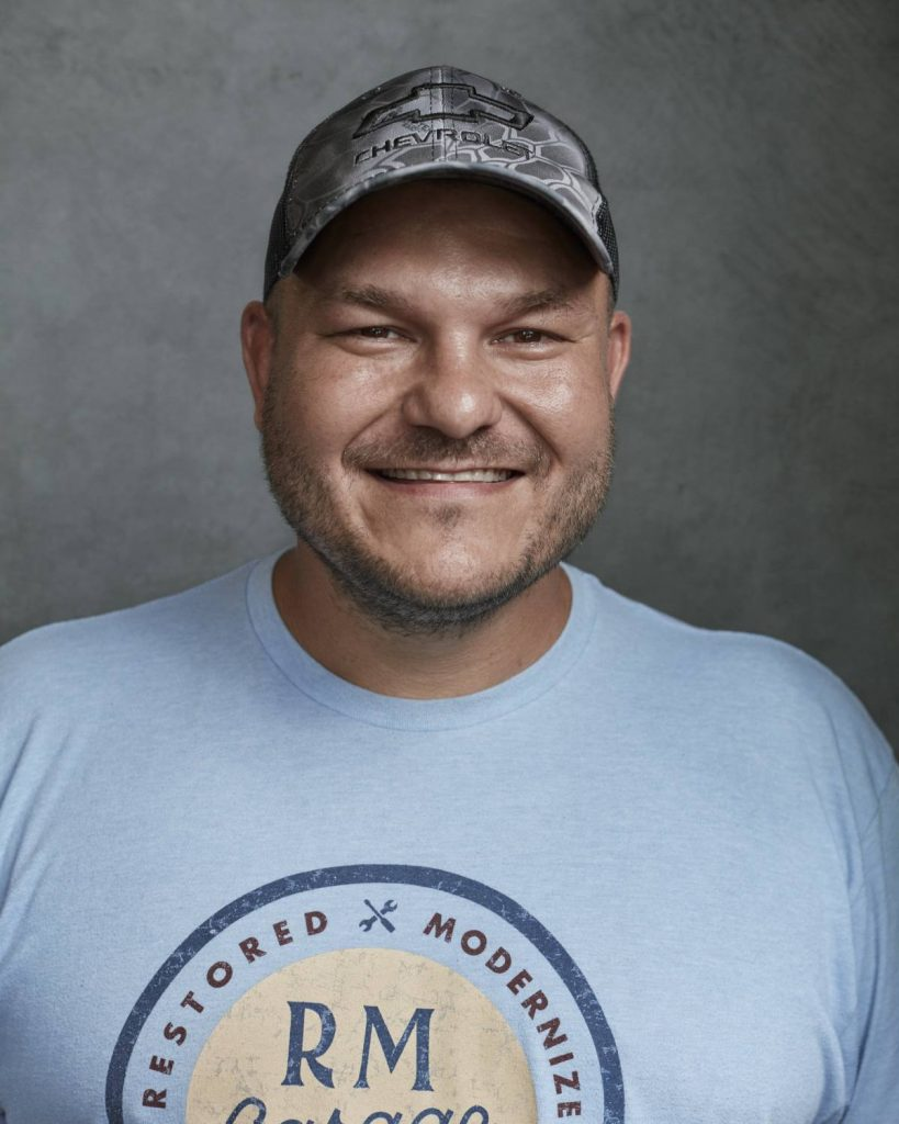 A portrait of Wayne Grega in front of a grey background