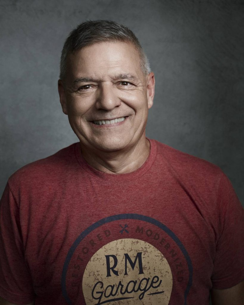 A portrait of Mark Stephenson in front of a grey background